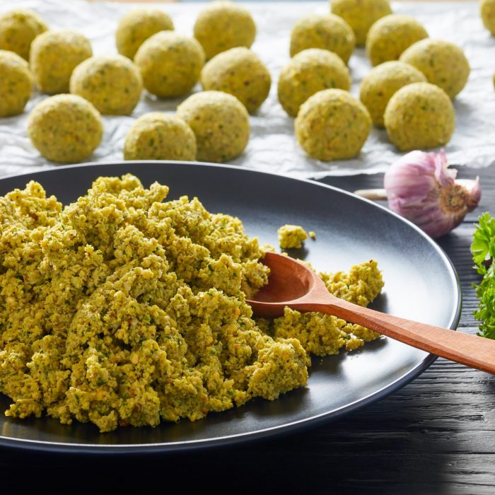 freshly ground chickpea mixed with greens and spices and raw falafel balls prepared to be fried or oven baked, middle eastern recipe, view from above, close-up
